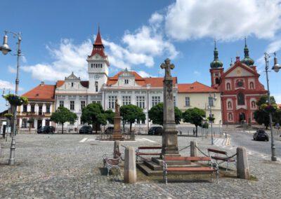 7. Staroboleslavská radnice se sochou sv. Václava v pozadí s Kostelem Nanebevzetí Panny Marie